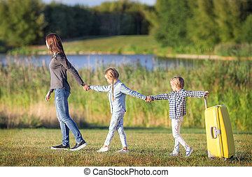 vidám család, noha, bőrönd, gyalogló, szabadban