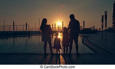 vidám család, noha, három gyerek, csodáló, a, napnyugta, kifejez in, a, felszín, közül, a, pocsolya