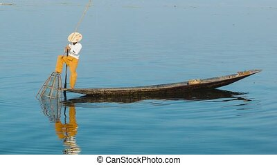 Burmese fisherman catches fish using a trap. Inle lake,...