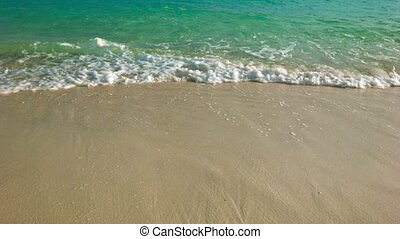 Clear water. Surf on a sandy tropical beach