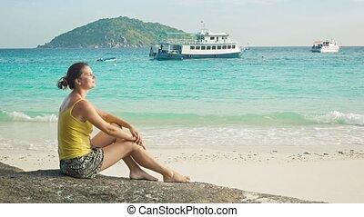 Girl sitting on a rock on seashore. Similan Islands, Thailand