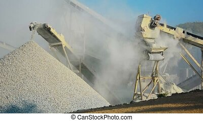 Video 1080p - Knapping machine unloads the crushed stone. All around in the dust.