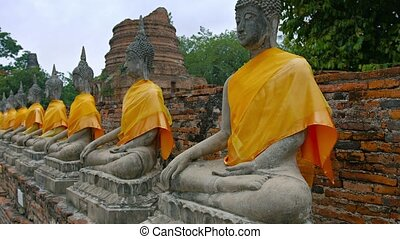 Long row of ancient, identical, hand-carved Buddha...