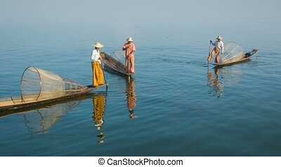 Myanmar, Inle Lake. Fishermen on boats with traditional...