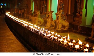 Oil lamps in a Buddhist temple at night. Burma, Yangon