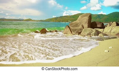 Sea surf on the beach with rocks and sand. Thailand, Phuket