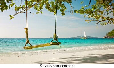 Swing on a background of the tropical sea with yachts