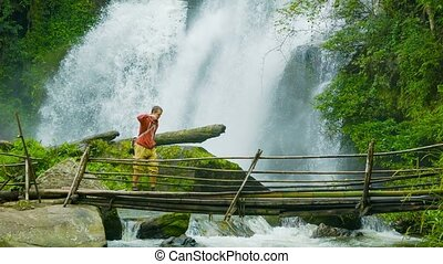Tourists on a bamboo bridge on the background of a waterfall. Doi Inthanon National park, Thailand