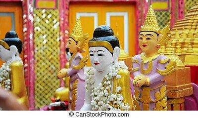 Watering Buddha figurine. Ritual in the Buddhist temple -...