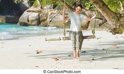 Young woman on a swing on the coast of tropical sea