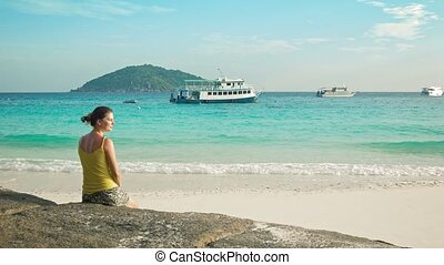 Young woman sitting on the beach and looks at the ships. Similan Islands, Thailand