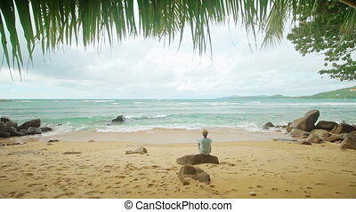 A lone man sits on the shore of a tropical ocean