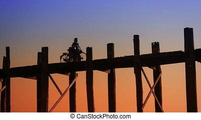 Man with bicycle at old bridge. Burma, Mandalay - Video...