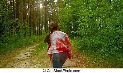Little girl runs on a footpath in a pine forest