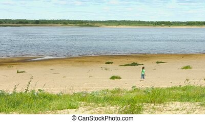 Lonely child walking along the shore of a large river