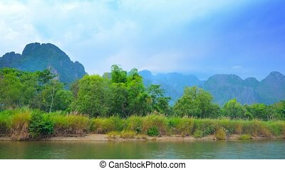 Coast of the small river and mountains in the background. Laos, Vang Vieng