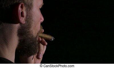 Video as a man smokes a big cigar. Black. Close up