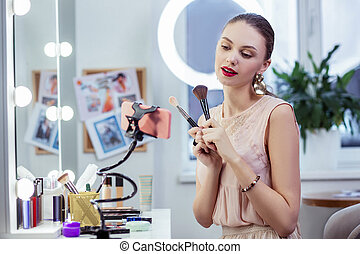 Nice young woman holding two makeup brushes