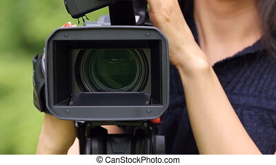 Video camera and female operator. - Woman operating video...