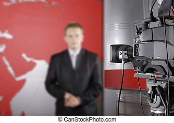 TV studio with close up of a video camera and an unrecognizable presenter in the background