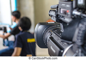 Video Camera has focus behind the photographer for broadcasting and recording.