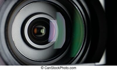 Video camera lens, showing zoom and glare, come to the...
