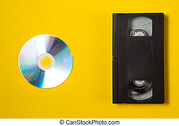 Video cassette videotape and compact disc on a yellow background. Top view. Save your memories on modern media. Flat lay concept.