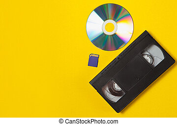 Video cassette videotape, compact disc, flash sd card on a yellow background. Top view. Video storage and recording technology. Flat lay concept.