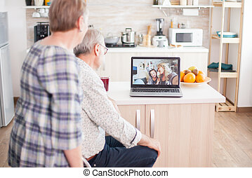 Senior couple talking with niece and daughter on online video call from kitchen. Elderly person using modern communication online internet web techonolgy.