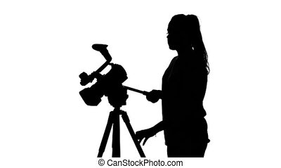 Video director manages a professional camera in the studio. White. Silhouette