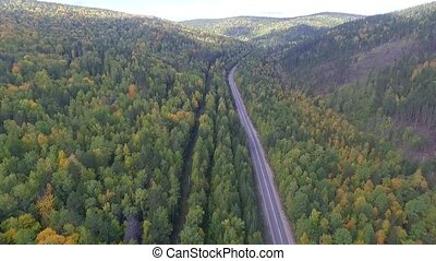 Video drone aerial view over the road in the forest on the way to Lake Baikal