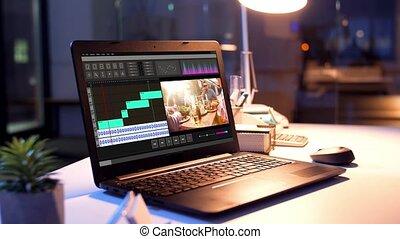 video editor program on laptop at night office - post...