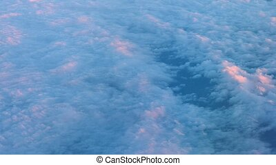Airborne shot of a layer of puffy, pink cottony clouds -...