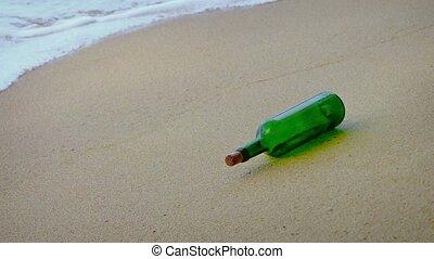 Green glass wine bottle rolls in the gentle waves on a sandy...