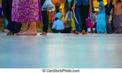 Legs of visitors of Buddhist temple without shoes. Myanmar, Yangon.