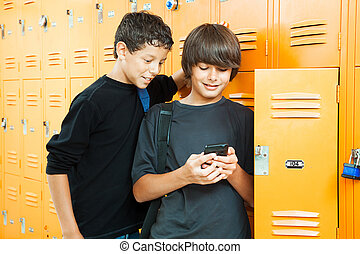 Video Game in School - Two teenage boys playing a handheld...