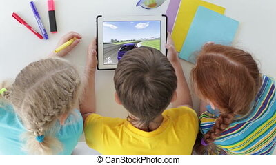 Video games - Boy playing video games on touchpad, girls...