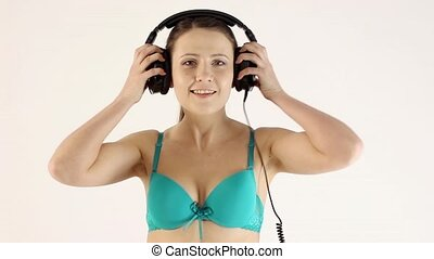 Video of a cute woman with headphones in lingerie