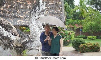 Asian senior couple under umbrella
