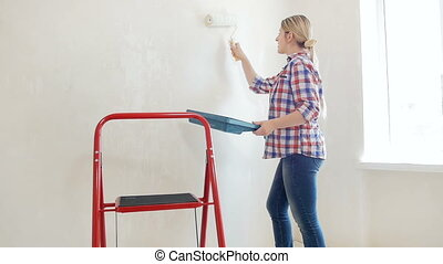 Video of beautiful smiling young woman painting walls in her house with white paint and roller