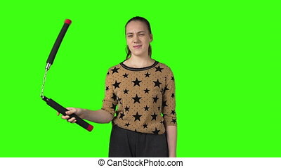 Video of young woman with nunchucks on green isolated background