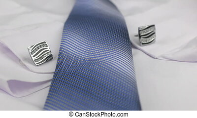 Video of blue tie and cufflinks lying on a white shirt. Dolly shot. Close-up.