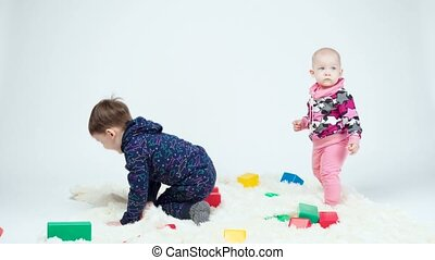 Video of brother and sister among toys on white background