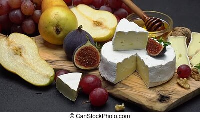 Video of brie or camembert cheese and grapes on wooden...
