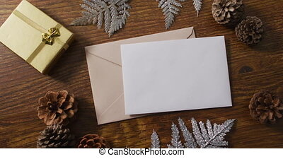 Video of christmas decorations with white card and beige envelope on wooden background. christmas, communication, tradition and celebration concept.