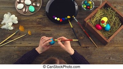 Video of female artist painting on Easter eggs preparing for christian religious holiday, top view. High quality 4k footage