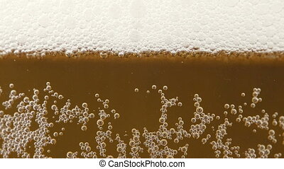 Video of gold cold beer in glass with little bubbles
