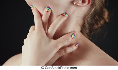 Close-up video of hands with rainbow manicure on nude neck