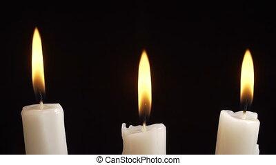 Video of burning candle on black background