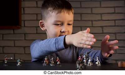 Video of four year old boy playing with tin soldiers